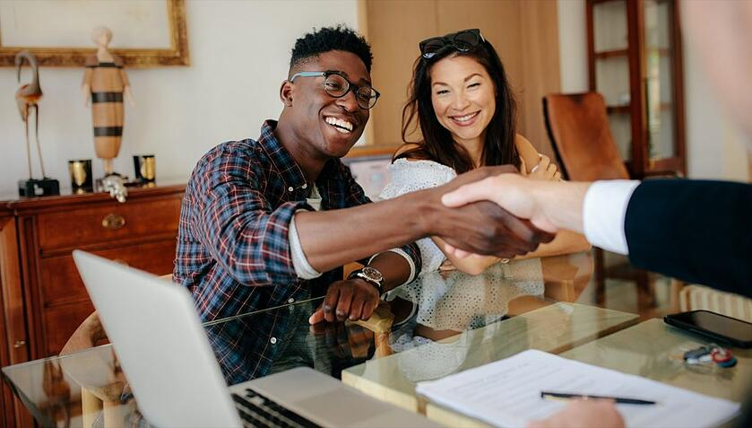 Two tenants shaking hands with new landlord after screening